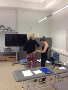 Frida is measuring Kirke's body fat percentage with skinfold measurement.