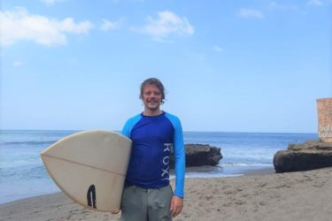 Michael Ringlein standing on a beach holding a surf board
